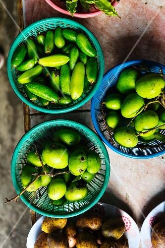 Green mangos in three bowls
