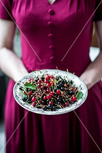 A woman holding a bowl of wild cherries