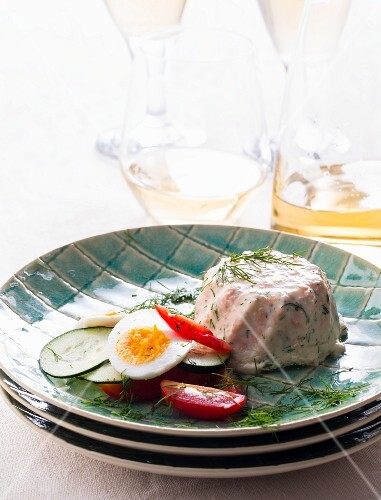 Salmon mousse with dill and a salad garnish on a plate