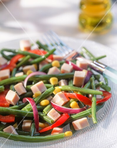 A summer salad with green beans, ham, peppers and corn