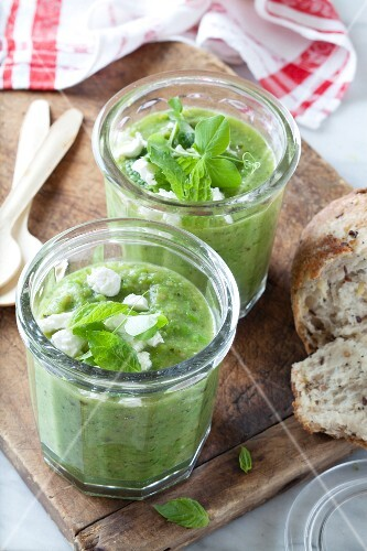 Cold pea and zucchini soup with mint and feta in glasses