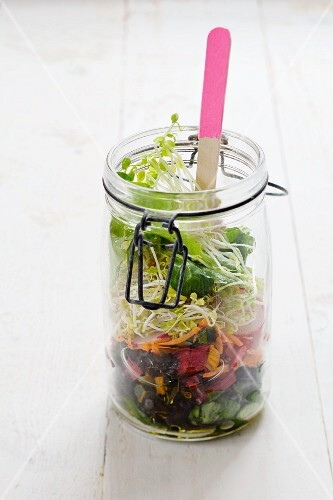 Salad in a glass jar with lambs lettuce, chard, carrots, radishes, lentil sprouts and pea sprouts