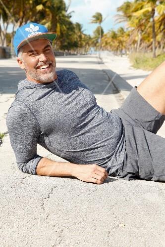A man in sportswear lying on a beach promenade