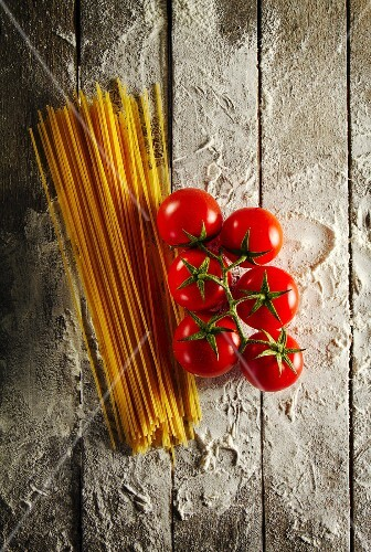 Cherry tomatoes with spaghetti and flour on a wooden table