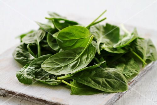 Fresh spinach leaves on a chopping board