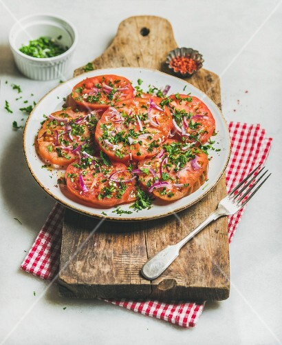 Fresh heirloom tomato, parsley and onion salad in white round plate on wooden board over light grey marble background