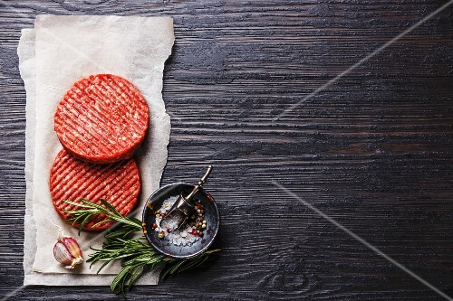 Raw Ground beef meat Burger steak cutlets and seasonings on black burned wooden background