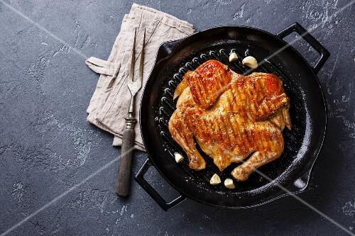 Grilled fried roast Chicken Tabaka in frying pan on dark stone background