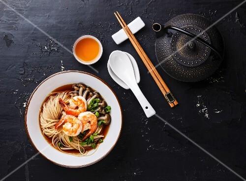Ramennudeln mit Garnelen und Pilzen serviert mit Tee (Asien)
