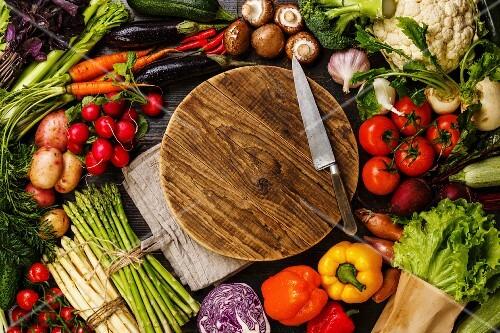 Fresh vegetables around round wooden cutting board copy space