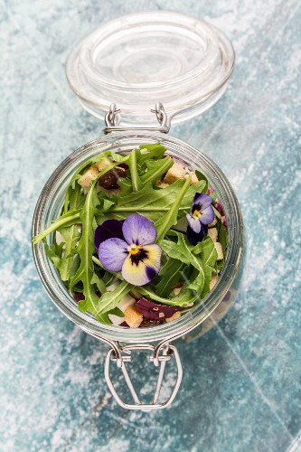 Quinoa salad with lambs lettuce, radicchio, rocket, croutons, goat's cheese and horned violets in a glass jar