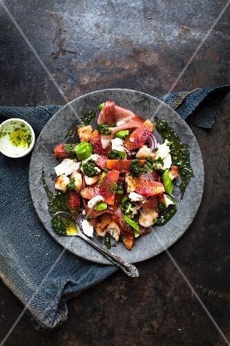 A salad with prosciutto, mozzarella, pesto, blood orange and bread