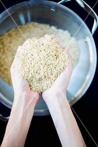 Hands holding uncooked wholemeal rice (seen from above)