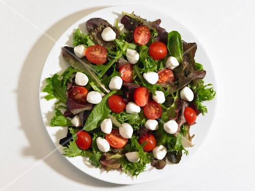 Cherry tomatoes and mini mozzarella balls on a bed of lettuce (seen from above)