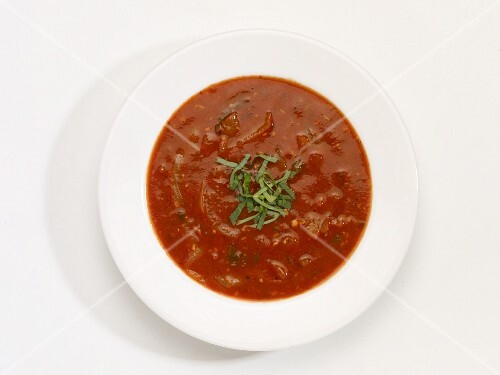 A bowl of tomato and onion soup in front of a white background (seen from above)