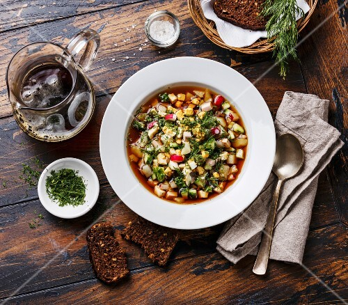 Cold Soup Okroshka with sausage, vegetables and kvass serving size on wooden table