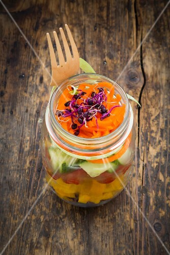 Rainbow salad in glass jars with red cabbage, yellow pepper, tomato, cucumber, carrots and beetroot sprouts
