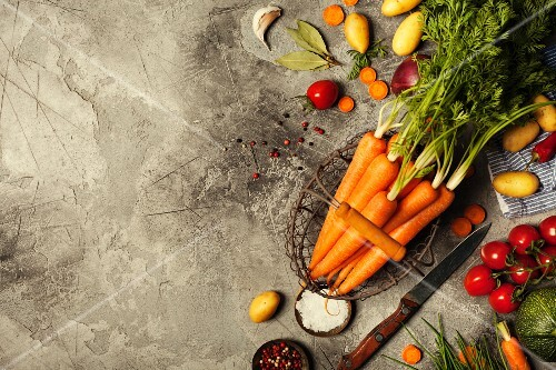 Fresh carrots bunch and vegetables on rustic grey stone background