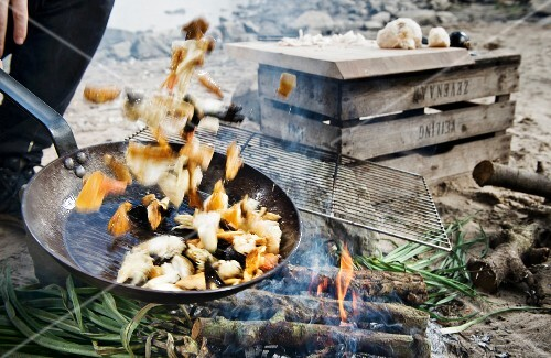 Camping food in a pan tossed over a camp fire
