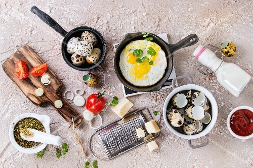 Breakfast with fried quail eggs in iron cast pan, cherry tomatoes, onion, ketchup sauce, seasonings in mortar, cheese grater, egg shell in pot