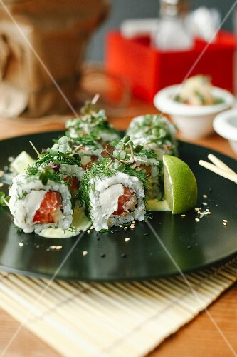 Sushi rolls with salmon, fresh cheese and herbs