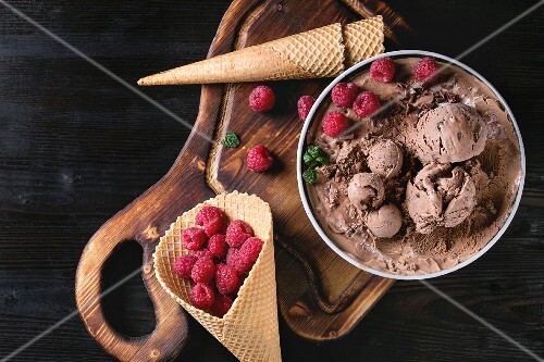Bowl of homemade chocolate ice cream with fresh raspberries, mint and waffle cone on wood serving board