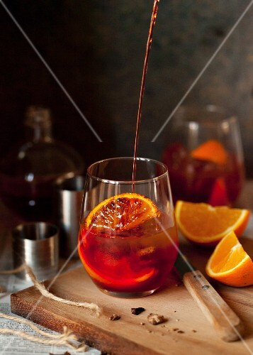 Negroni Cocktail in Glas gießen