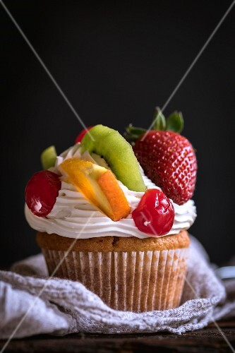 A cupcake with fresh fruit and cream