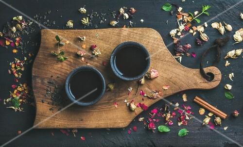 Chinese black tea in black stoneware cups on serving wooden board over black wooden background with herbs, flower buds, tea leaves spilt around