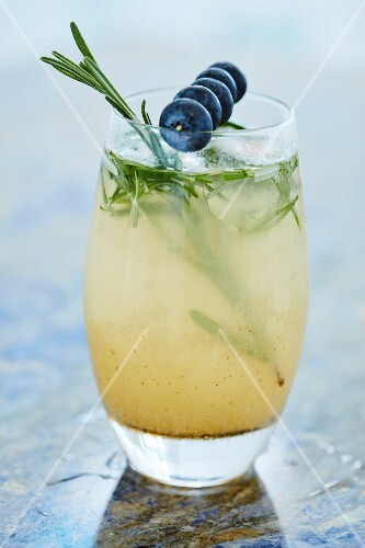A refreshing cocktail with rosemary and blueberries on a cocktail stick