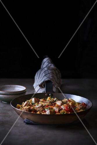 Calamarata pasta with swordfish ragout in the pan