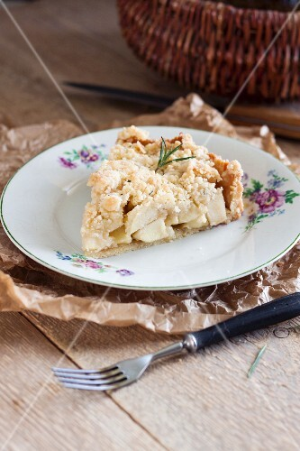 Slice of a rustic apple pie with rosemary