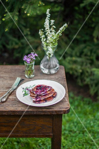 Pancakes with blueberries and blueberry sauce, served in the garden