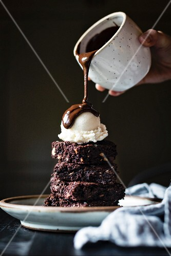 A brownie sundae drizzled with chocolate sauce