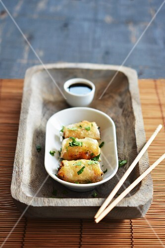 Spring rolls in a bowl with soy sauce on a rustic tray with chopsticks