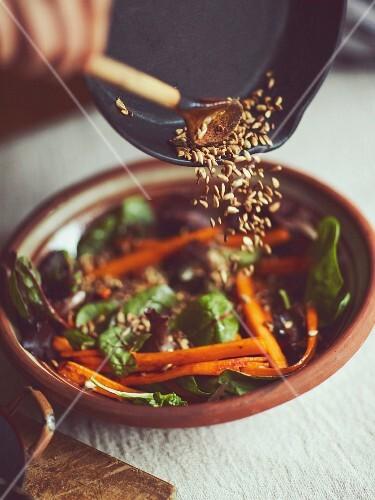 Karamellisierte Karotten mit gemischtem Blattsalat und gerösteten Pinienkernen