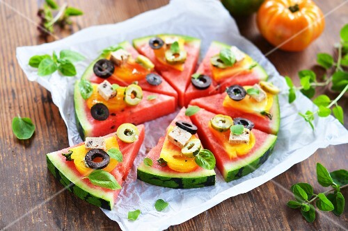 A melon 'pizza' garnished with tomatoes, tofu, olives and fresh herbs