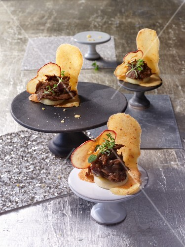 Duck canapes with dried apple slices on spicy wafer biscuits