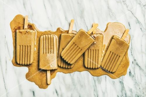 Schmelzendes veganes Milchkaffee-Eis am Stiel auf Marmoruntergrund