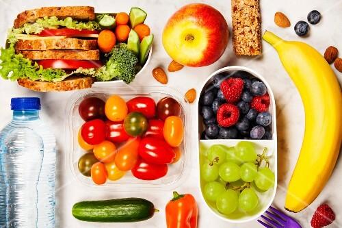 Gesunde Lunch-Box mit Sandwich dazu frisches Gemüse, Früchte und Flasche Wasser