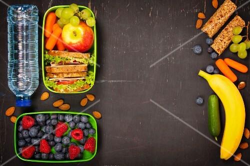 Gesunde Lunch-Box mit Sandwich, Obst, Gemüse und Flasche Wasser