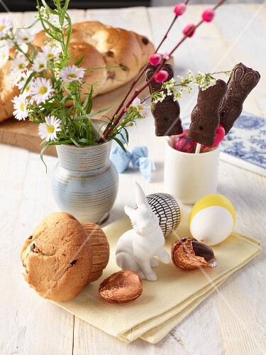 Vegan Easter bread, chocolate rabbits, chocolate eggs and a bouquet of flowers