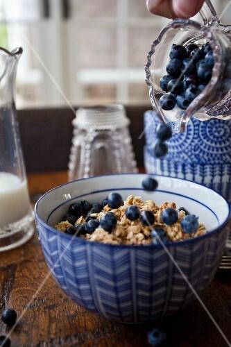 Frau schüttet Heidelbeeren auf Cerealien in Müslischale