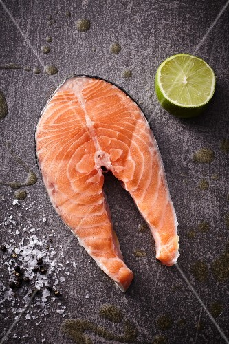 A raw salmon steak with half a lime, salt and pepper