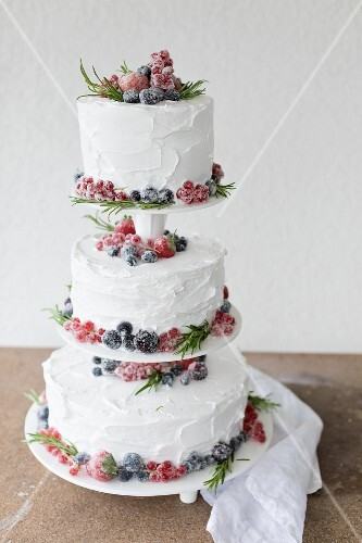 A three-tiered wedding cake with sugar-coated berries