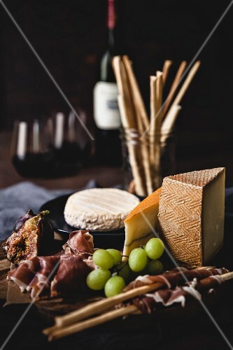 Prosciutto and cheese on a wooden board with grapes and wine