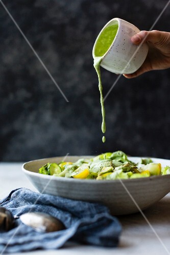 Gemüsesalat wird mit veganem Kräuter-Cashew-Dressing beträufelt