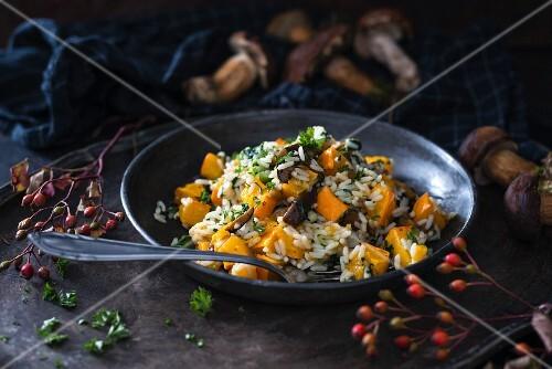 Vegan rice dish in a pan with pumpkin and wild mushrooms