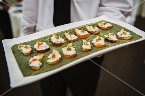 Waiter serving hors d'oeuvres of toast with cheese and herbs at an event
