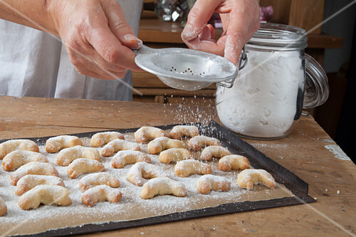 Gluten-free vanilla crescent biscuits being dusted with icing sugar